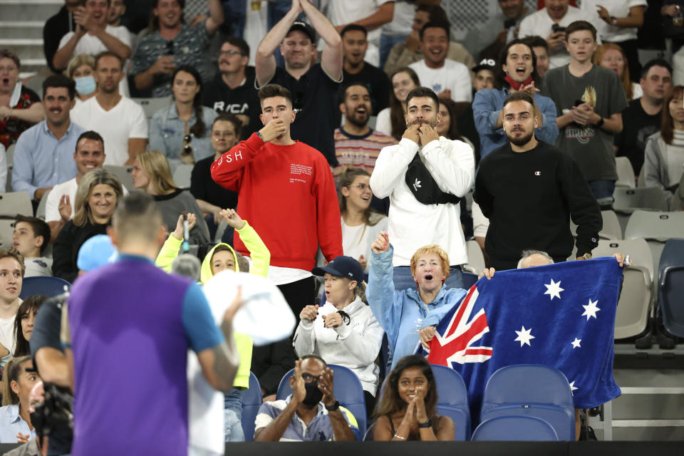 Fans cheer for Australia's Nick Kyrgios, back to camera, during his third round match against Austria's Dominic Thiem at the Australian Open tennis championship in Melbourne, Australia, Friday, Feb. 12, 2021.(AP Photo/Hamish Blair)