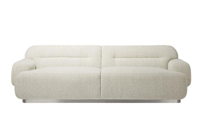 "This undated photo shows CB2's Logan sofa. Designer John McClain, whose studio is in Orlando, says one big trend he's seeing in fall décor is a range of deep, cozy textures like boucle and shearling. ""(They're) are cropping up on more than just pillows these days – entire sofas, chairs and headboards are sporting luscious upholstery reminiscent of lambs, puppies and ponies."" CB2 has several options, including the Gwyneth side chair, Logan sofa and Azalea chair. (CB2 via AP)"