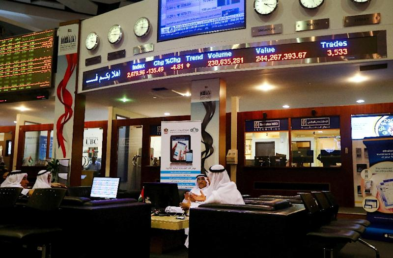 Traders sit at the Dubai bourse