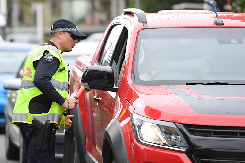 Police check permits at Griffith Street checkpoint at Coolangatta on the Gold Coast. Source: AAP