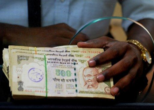 An employee waits to deposit Indian rupee notes at a bank in Mumbai