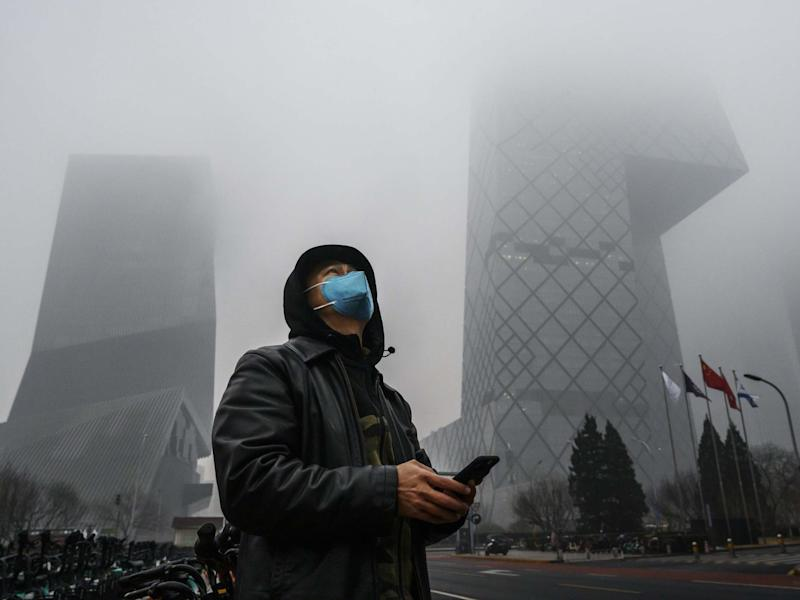 A Chinese man wears a protective mask as he stands near the CCTV building in fog and pollution during rush hour in Beijing's central business district: Getty Images