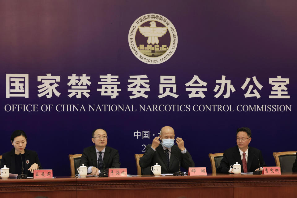 Deng Ming, deputy director of China's National Narcotics Control Commission, center removes his mask for a press conference in Beijing on Tuesday, May 11, 2021. China on Tuesday said it will add all synthetic cannabinoids to its list of banned drugs, in what it described as a first in the world, to curb their manufacturing, trafficking and abuse. (AP Photo/Ng Han Guan)