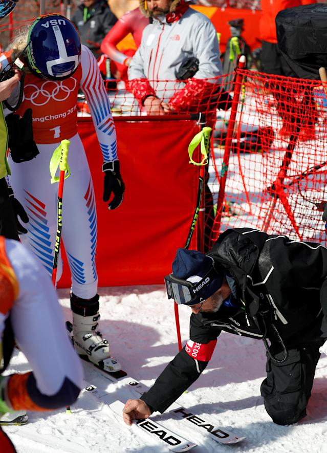 """Heinz Haemmerle, or """"Magic Heinzi"""" as US skier Lindsey Vonn calls her Austrian-born ski technician, cleans the skis of the world's most successful skiing woman before the start of Vonn's third Olympic Downhill training run at the Winter Olympics 2018 in Pyeongchang, South Korea February 20, 2018. REUTERS/Leonhard Foeger"""