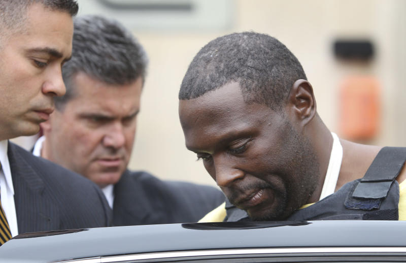 Darrell Fuller is escorted into a waiting car at a police station in Mineola, N.Y., Thursday, Oct. 25, 2012. The ex-convict suspected of gunning down a New York police officer and then fatally shooting a carjacking victim is charged with first-degree murder. (AP Photo/Seth Wenig)