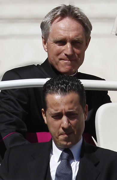 """FILE - In this Wednesday, April 18, 2012 file photo, Pope Benedict XVI's then-butler Paolo Gabriele, bottom, and personal secretary Georg Gaenswein sit in the car with the pontiff, not seen, as he arrives in St. Peter's Square at the Vatican for a general audience. Pope Benedict XVI's ex-butler Paolo Gabriele and another Vatican lay employee, Claudio Sciarpelletti, are scheduled to go on trial Saturday, Sept. 29, 2012, in the embarrassing theft of papal documents that exposed alleged corruption at the Holy See's highest levels. Gabriele was arrested May 24 after Vatican police found what prosecutors called an """"enormous'' stash of documents from the pope's desk in his Vatican City apartment. (AP Photo/Alessandra Tarantino, File)"""