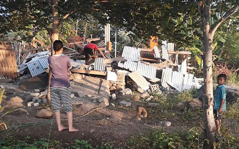 An Indonesian person scrambles over the collapsed ruins of a house as others look on following an earthquake in Lombok - AFP
