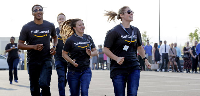 Amazon workers run past a line of applicants waiting to enter a job fair, Wednesday, Aug. 2, 2017, at an Amazon fulfillment center, in Kent, Wash. (AP Photo/Elaine Thompson)