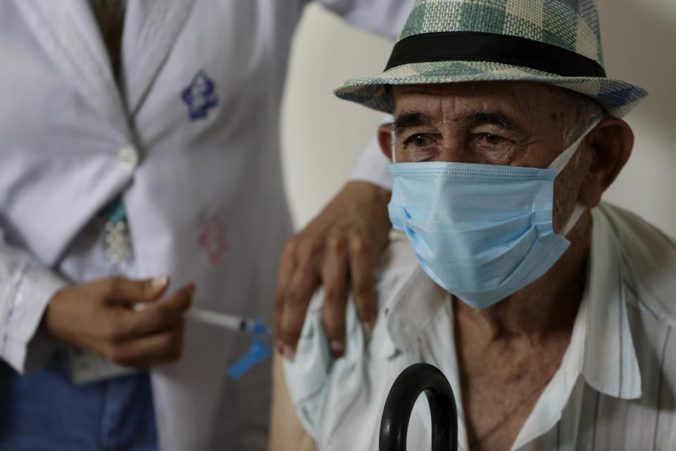 Emidio Dorel, 81, who has already been infected with the new Coronavirus, gets a shot of China's Sinovac CoronaVac vaccine during the resumption of priority vaccination at a vaccination center in Brasilia, Brazil, Wednesday, Feb. 17, 2021. The local government resumed its vaccination program for the priority group of elderly people over 79 years, after the four-day carnival recess. (AP Photo/Eraldo Peres)