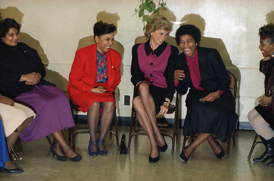 """FILE - In this file photo dated Feb. 2, 1989, Princess Diana, centre smiles as Henry Street Settlement Director Verona Middleton-Jeter laughs, at New York's Henry Street Settlement, USA. For someone who began her life in the spotlight as """"Shy Di,"""" Princess Diana became an unlikely, revolutionary during her years in the House of Windsor. She helped modernize the monarchy by making it more personal, changing the way the royal family related to people. By interacting more intimately with the public -- kneeling to the level of children, sitting on edge of a patient's hospital bed, writing personal notes to her fans -- she set an example that has been followed by other royals as the monarchy worked to become more human and remain relevant in the 21st century. (AP Photo/Richard Drew, File)"""