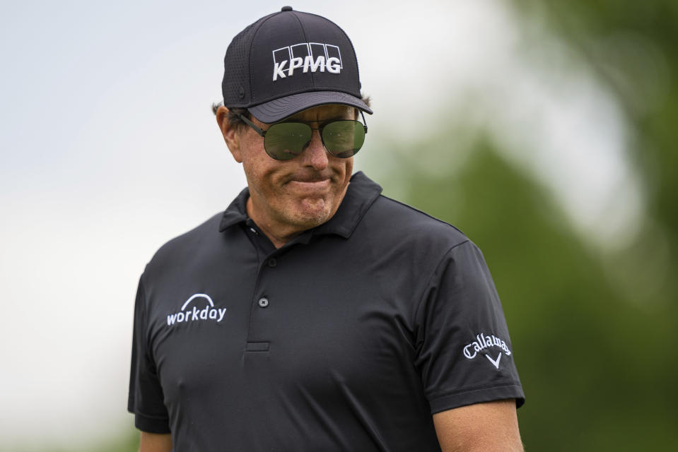 Phil Mickelson looks down after finishing on the first hole during the third round of the Wells Fargo Championship golf tournament at Quail Hollow on Saturday, May 8, 2021, in Charlotte, N.C. (AP Photo/Jacob Kupferman)