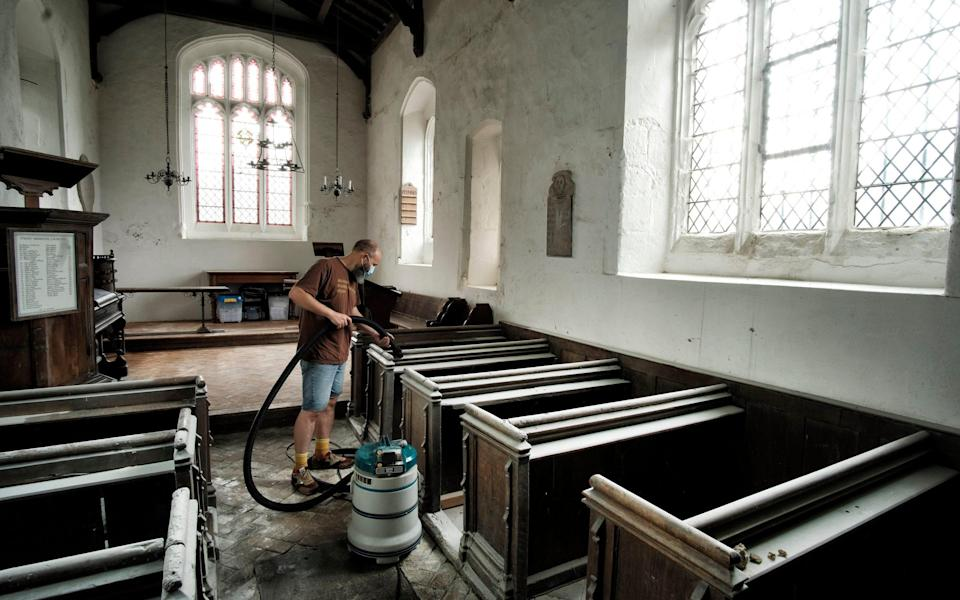Volunteers clean up after St Mary Magdalene Caldecote in Hertfordshire was vandalised - John Robertson for The Telegraph