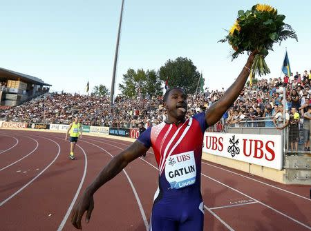 Justin Gatlin of the U.S. raises a bouquet of flowers after winning the men's 100m race during the Lausanne Diamond League meeting at the Stade de la Pontaise in Lausanne