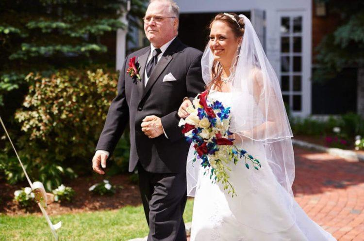 father and bride walking down the aisle at outdoor wedding