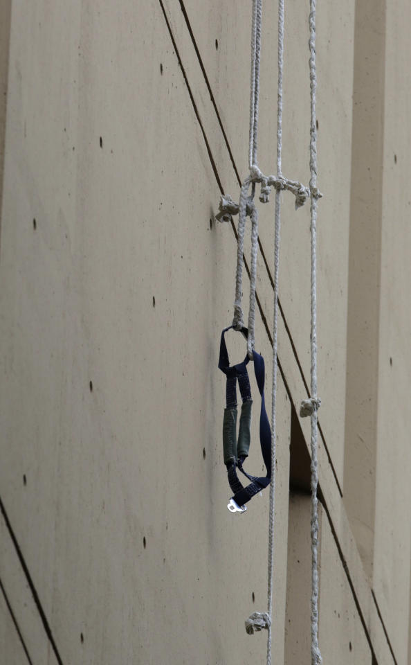 A harness and the end of a rope dangles from a window on the back side of the Metropolitan Correctional Center Tuesday, Dec. 18, 2012, in Chicago. Two convicted bank robbers used a knotted rope or bed sheets to escape from the federal prison window high above downtown Chicago early Tuesday, a week after one of them made a courtroom vow of retribution, to federal judge. The escape occurred sometime between 5 a.m. and 8:45 a.m. when the inmates were discovered missing, Chicago Police Sgt. Mark Lazarro said. Hours later, what appeared to be a rope, knotted at six-foot intervals, could be seen dangling into an alley from a window of the Metropolitan Correctional Center approximately 20 stories above the ground. (AP Photo/M. Spencer Green)