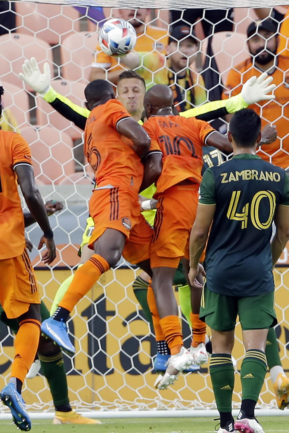Houston Dynamo's Maynor Figueroa (15) and Fafa Picault (10) both go for a header for a goal as Portland Timbers goalkeeper Aljaz Ivacic, back, attempts to block during the first half of an MLS soccer match Wednesday, June 23, 2021, in Houston. Picault was credited with the goal. (AP Photo/Michael Wyke)