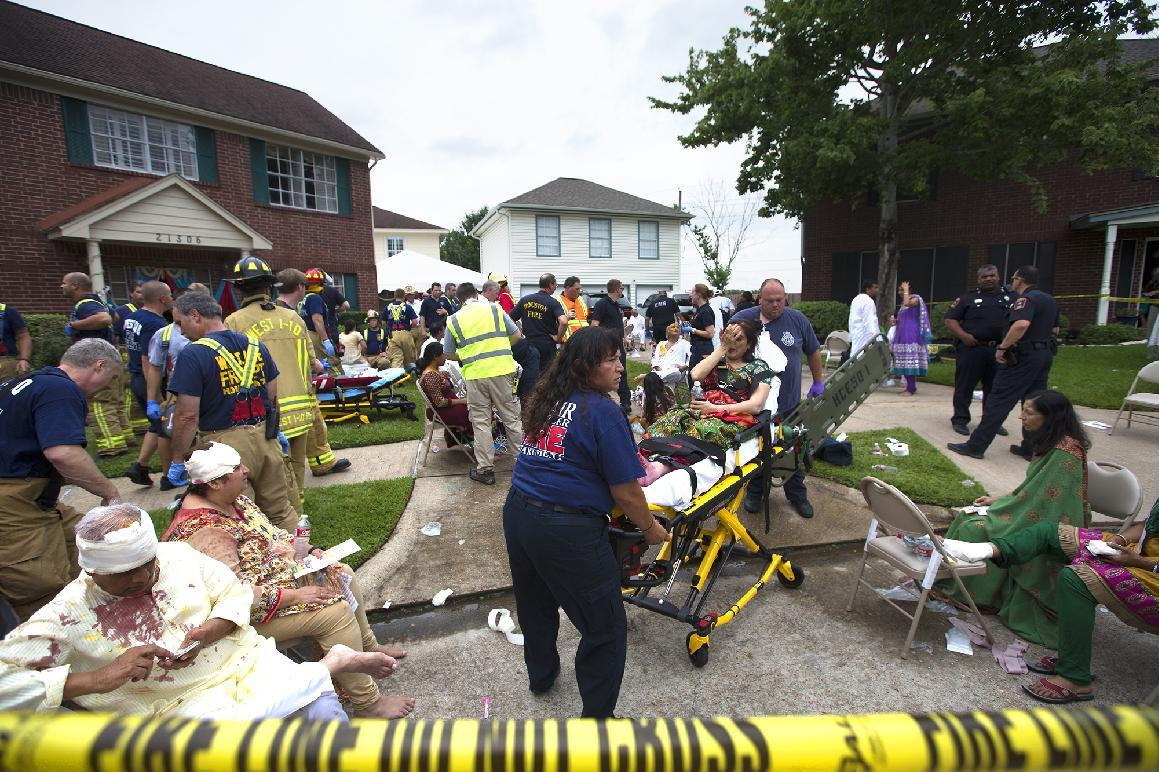 Firefighters and emergency crews treated people outside in a makeshift triage area set up in the front yards of nearby homes after a floor collapsed under a large crowd of people gathered for a religious event Thursday, June 26, 2014, in Katy, Texas. People were in a room above a detached garage when the floor gave way, though it wasn't immediately clear how many people were inside at the time, West I-10 Fire Department spokesman Tim Thomas said. (AP Photo/Houston Chronicle, Cody Duty) MANDATORY CREDIT