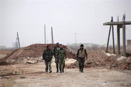 Forces loyal to Syria's President Bashar al-Assad carry their weapons as they walk along a road in the town of Tel Arn in Aleppo after capturing it from rebels