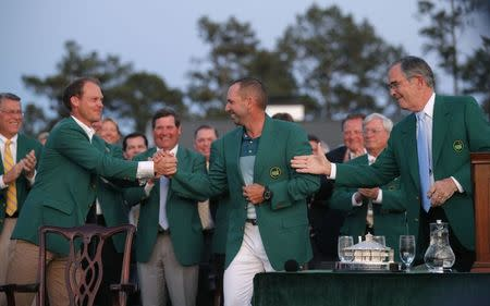 Sergio Garcia of Spain shakes hands with Danny Willett of England (L) and Augusta National chairman Billy Payne after being presented his green jacket after winning the 2017 Masters golf tournament at Augusta National Golf Club in Augusta, Georgia, U.S., April 9, 2017. REUTERS/Brian Snyder