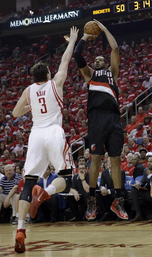 Portland Trail Blazers' LaMarcus Aldridge (12) shoots as Houston Rockets' Omer Asik (3) defends during the second quarter in Game 2 of an opening-round NBA basketball playoff series Wednesday, April 23, 2014, in Houston. (AP Photo/David J. Phillip)