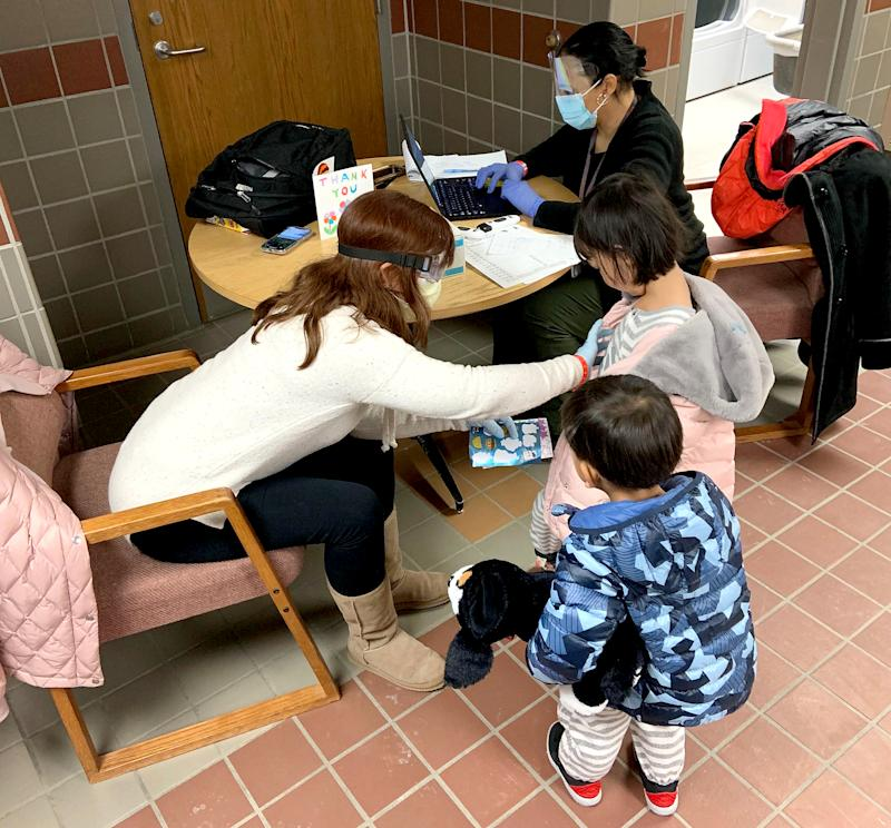 A CDC employee performs a final health check on children who were evacuated from Wuhan, and completed their mandatory 14-day quarantine at Camp Ashland in Nebraska.
