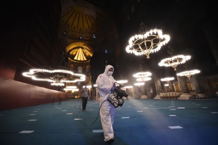 A few hours before prayers for the Islamic festival of Eid al-Adha, a municipality worker wearing protective clothing against the spread of coronavirus sprays disinfectant in the Byzantine-era Hagia Sophia, recently converted back to a mosque, in the historic Sultanahmet district of Istanbul, early Friday, July 31, 2020. This is the first Feast of Sacrifice since the onset of the coronavirus pandemic. The major Muslim holiday, at the end of the hajj pilgrimage to Mecca, is observed around the world by believers and commemorates prophet Abraham's pledge to sacrifice his son as an act of obedience to God. (AP Photo/Yasin Akgul)
