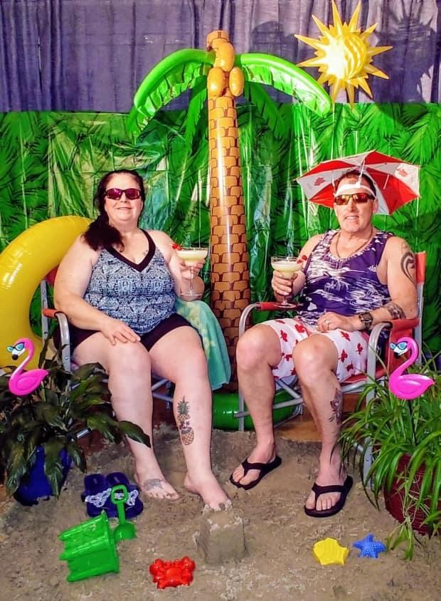 Ruth and OJ Gallant enjoy a cocktail in their living room, which they've decorated to look more like a Florida beach, right down to the sand. With the pandemic still putting real travel on hold, the couple has embraced elaborate staycations and shared photos to lift others' spirits. (Submitted by Ruth Gallant - image credit)