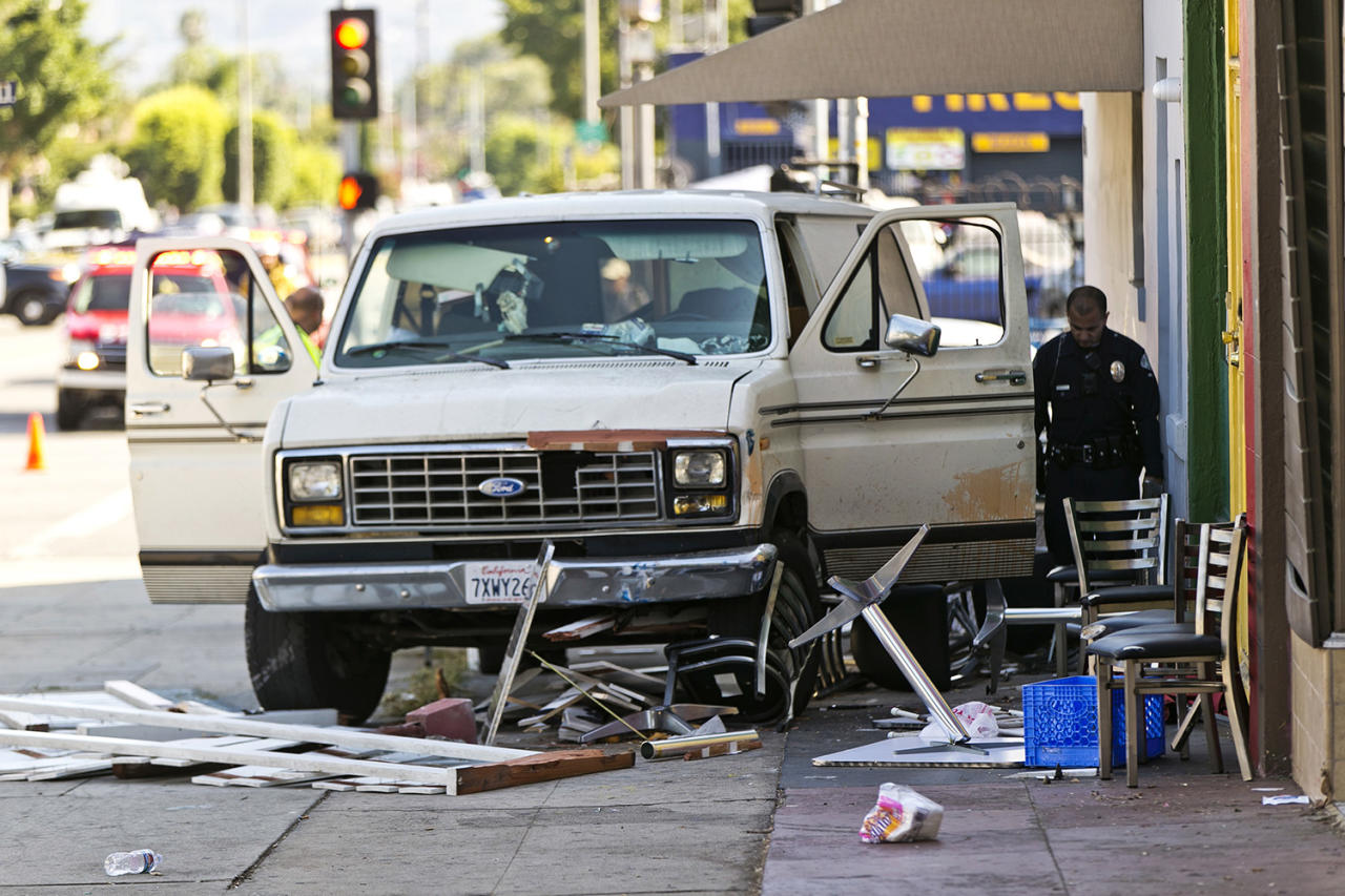 <p>An official looks into a van that plowed into a group of people on a Los Angeles sidewalk on Sunday, July 30, 2017. A witness to the crash told The Associated Press the van jumped a curb and careened into a group of people eating outside The Fish Spot restaurant in the city's Mid-Wilshire neighborhood. The cause of the crash is under investigation. (AP Photo/Damian Dovarganes) </p>