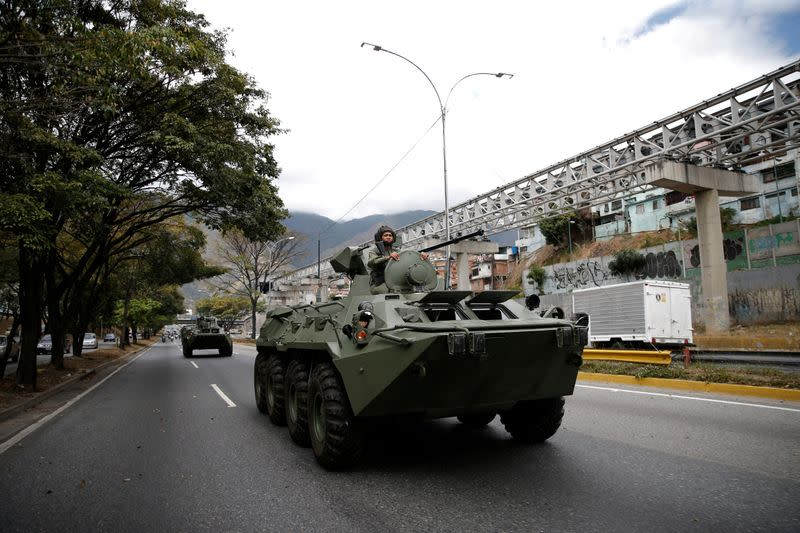 A soldier is seen over an armored vehicle driven along a highway during a military exercise in Caracas