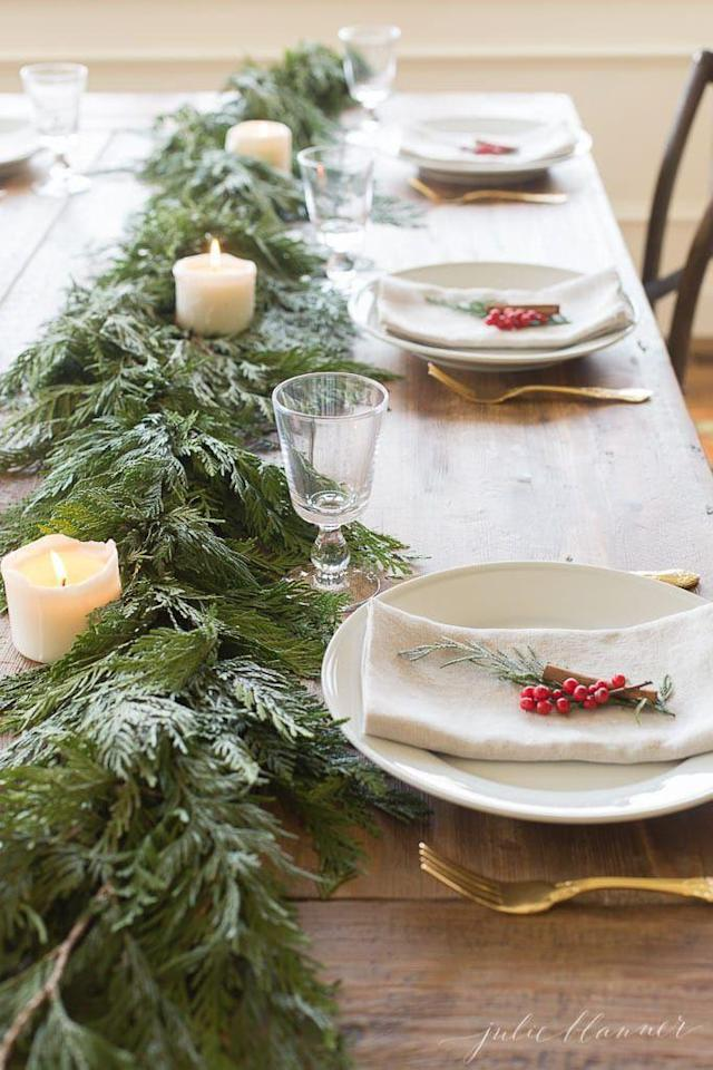 """<p>With fresh and fragrant greenery, red berries, and glowing candles, this elegant combination has all the ingredients for a merry gathering.</p><p><strong>Get the tutorial at <a href=""""https://julieblanner.com/garland-centerpiece/"""" rel=""""nofollow noopener"""" target=""""_blank"""" data-ylk=""""slk:Julie Blanner"""" class=""""link rapid-noclick-resp"""">Julie Blanner</a>.</strong></p><p><strong><a href=""""https://www.amazon.com/Bilipala-Artificial-Berries-Stamens-Ornaments/dp/B01M8PQIOH/"""" rel=""""nofollow noopener"""" target=""""_blank"""" data-ylk=""""slk:SHOP RED BERRIES"""" class=""""link rapid-noclick-resp"""">SHOP RED BERRIES</a><br></strong></p>"""