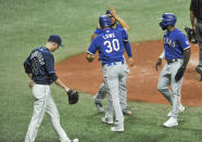 Tampa Bay Rays' Ryan Yarbrough (48) walks past Texas Rangers' Jose Trevino, left, Nate Lowe (30) and Adolis Garcia after they scored on Nick Solak's bases-loaded double during the fourth inning of a baseball game Tuesday, April 13, 2021, in St. Petersburg, Fla. (AP Photo/Steve Nesius)