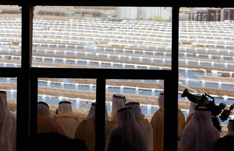 UAE officials are seen from behind a glass door as they look from a balcony at the Shams 1, Concentrated Solar power (CSP) plant, in al-Gharibiyah district on the outskirts of Abu Dhabi, on March 17, 2013 during the inauguration of the facility. Oil-rich Abu Dhabi officially opened the world's largest Concentrated Solar Power (CSP) plant, which cost $600 million to build and will provide electricity to 20,000 homes. AFP PHOTO/MARWAN NAAMANI