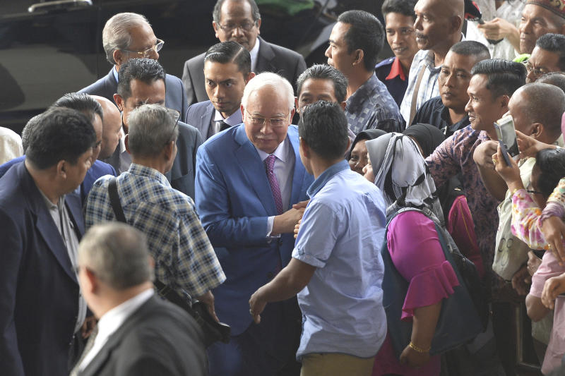 CORRECTS DATE - Former Malaysian Prime Minister Najib Razak, center, arrives at a court house in Kuala Lumpur, Malaysia for his corruption trial Tuesday, Dec. 3, 2019. (AP Photo)