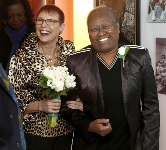 Patricia Ewert, left, and Vernita Gray, enter their living room for their wedding ceremony, the first gay marriage in Illinois, Wednesday, Nov. 27, 2013, in Chicago. U.S. District Judge Thomas Durkin on Monday, Nov. 25, 2013, ordered the Cook County clerk to issue an expedited marriage license to Gray and Ewert before the state's gay marriage law takes effect in June 2014, because Gray is terminally ill. (AP Photo/Charles Rex Arbogast)