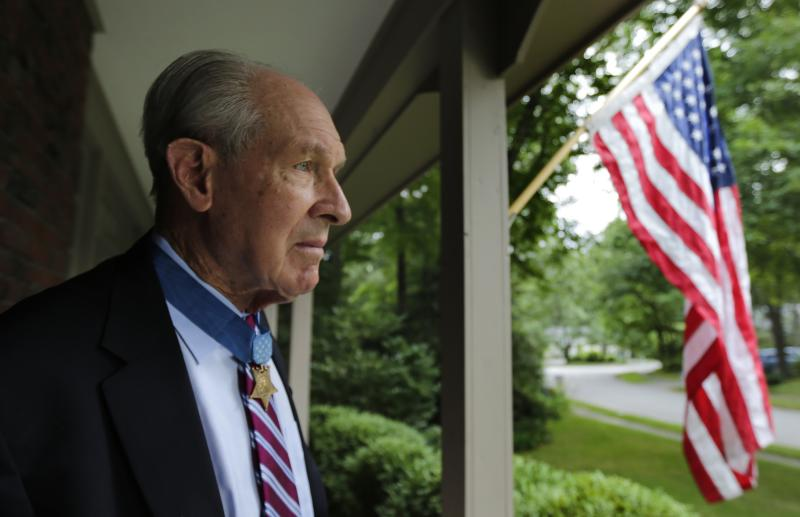 In this Friday, July 12, 2013 photo, retired U.S. Navy Capt. Thomas Hudner, who was awarded the Medal of Honor by President Truman, poses on the porch at his home in Concord, Mass., Friday, July 12, 2013. Two years after he made history by becoming the Navy's first black pilot, Ensign Jesse Brown lay trapped in his downed fighter plane in subfreezing North Korea, his leg broken and bleeding. His wingman crash-landed to try to save him, and even burned his hands trying to put out the flames. A chopper hovered nearby. Lt. j.g. Hudner could save himself, but not his friend. Hudner heads to Pyongyang on Saturday, July 20, 2013 with hopes of traveling in the coming week to the region known in North Korea as the Jangjin Reservoir, accompanied by soldiers from the Korean People's Army, to the spot where Brown died in December 1950. (AP Photo/Charles Krupa)