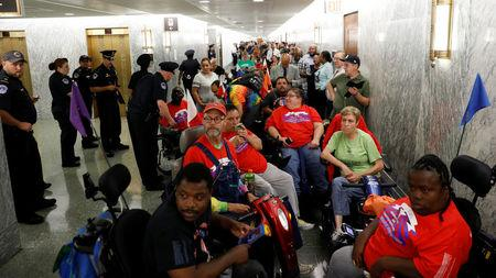 Protesters, mostly handicapped, line the hallway outside the Senate Finance Committee hearing room hours ahead a hearing on the latest Republican effort to repeal Obamacare on Capitol Hill in Washington, U.S., September 25, 2017. REUTERS/Kevin Lamarque