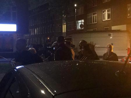 People gather at the scene where police are investigating a van with Spanish licence plates containing gas bottles which was found near a concert hall in Rotterdam