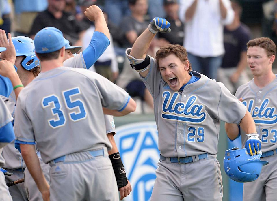 UCLA's Ty Moore (29) is greeted Chase Radan (35) and others after hitting a two-run home run in the sixth inning against Cal State Bakersfield during an NCAA college baseball tournament regional game in Los Angeles on Sunday, May 31, 2015. (AP Photo/Jayne Kamin-Oncea)