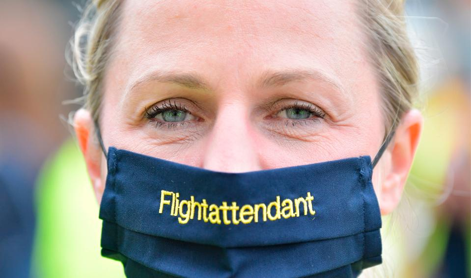 A flight attendant wears a face mask as employees of German flight operator Lufthansa demonstrate on June 24, 2020 in Berlin, in order to call on investors to back a bailout plan hammered out to rescue the airline hit by the coronavirus crisis. - The survival of Europe's top airline group Lufthansa is at stake on June 25, 2020, as shareholders are called to vote on a hard-fought nine billion euro ($10.2 billion) government rescue package. (Photo by Tobias SCHWARZ / AFP) (Photo by TOBIAS SCHWARZ/AFP via Getty Images)