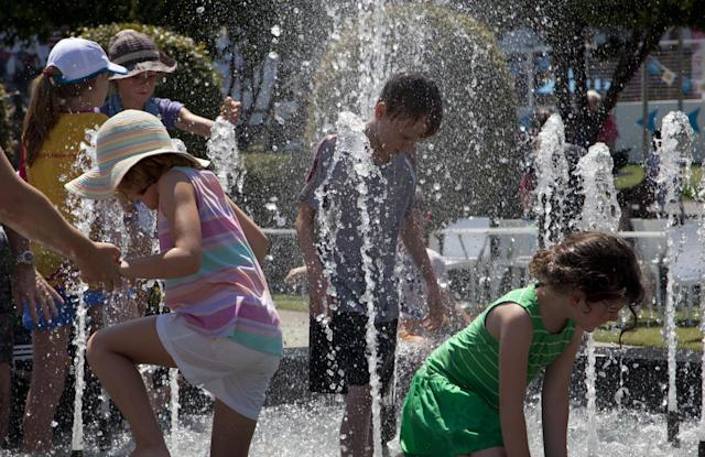 Spectators cool down in a fountain in Garden Square as play was suspended when organizers implemented the Extreme Heat policy during second round matches at the Australian Open tennis championship in Melbourne, Australia, Thursday, Jan. 16, 2014. (AP Photo/Joshua Baker)