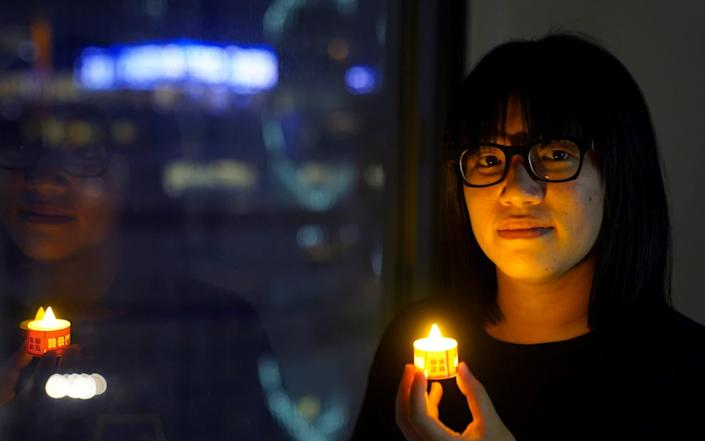 Chow Hang Tung poses with a candle ahead of the 32nd anniversary of the crackdown on pro-democracy demonstrators at Beijing's Tiananmen Square - Reuters