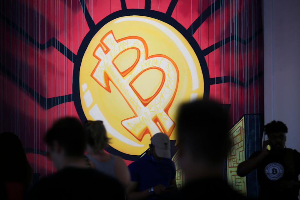 A banner (designed by artists Stacey Coon, Anastasia Sultzer, and Nanu Berks) with the logo of bitcoin is seen during the crypto-currency conference Bitcoin 2021 Convention at the Mana Convention Center in Miami, Florida, on June 4, 2021. (Photo by Marco BELLO / AFP) / The mention[s] appearing in the metadata of this photo by Marco BELLO has been modified in AFP systems adding the credit of the artists who designed the banner in the background : Stacey Coon, Anastasia Sultzer, and Nanu Berk. Please immediately remove previous versions from all your online services and delete it (them) from your servers. If you have been authorized by AFP to distribute it (them) to third parties, please ensure that the same actions are carried out by them. Failure to promptly comply with these instructions will entail liability on your part for any continued or post notification usage. Therefore we thank you very much for all your attention and prompt action. We are sorry for the inconvenience this notification may cause and remain at your disposal for any further information you may require. (Photo by MARCO BELLO/AFP via Getty Images)