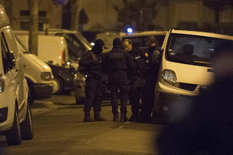 Police officers and members of a mine-clearing team gather in a street during a raid in the Argenteuil neighbourhood northwest of Paris on March 24, 2016 (AFP Photo/Geoffrety Van De Hasselt )