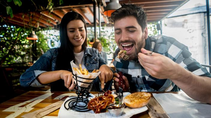 Loving couple eating together at a burgerâ??s restaurant and looking happy on a date.