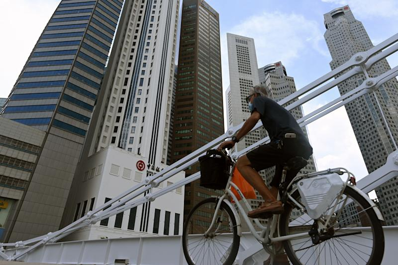 A man rides a bicycle past commercial buildings in the financial business district in Singapore on June 11, 2020, as the city state eased its partial lockdown restrictions aimed at curbing the spread of the COVID-19 coronavirus. (Photo by ROSLAN RAHMAN / AFP) (Photo by ROSLAN RAHMAN/AFP via Getty Images)