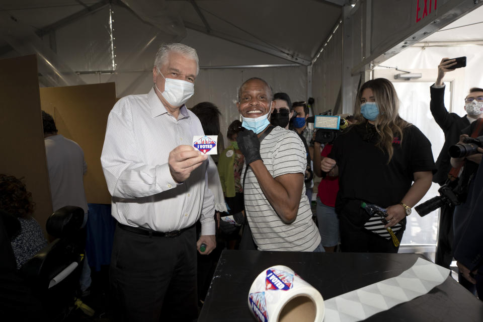 Nevada Governor Steve Sisolak, left, poses with poll worker Toni James after dropping off his ballot at an early voting site in Las Vegas Saturday, Oct. 17, 2020. (Steve Marcus/Las Vegas Sun via AP)