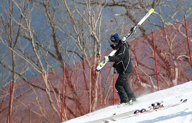 """Heinz Haemmerle, or """"Magic Heinzi"""" as US skier Lindsey Vonn calls her Austrian-born ski technician, skis down with an unused pair of skis of the world's most successful skiing woman after Vonn left the starting house for her third Olympic Downhill training run at the Winter Olympics 2018 in Pyeongchang, South Korea, February 20, 2018. REUTERS/Leonhard Foeger"""