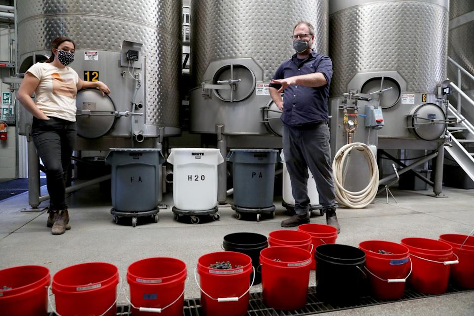 """Dan Petroski, right, chief wine maker of Larkmead Vineyards, prepares Cabernet Sauvignon grapes for a mock fermentation to check grape maturity and color development in the tank room at Larkmead Vineyards in Pope Valley. <span class=""""copyright"""">(Gary Coronado / Los Angeles Times)</span>"""