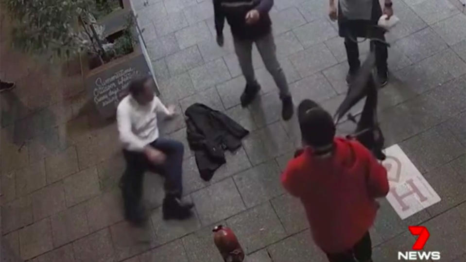 Another person wields a stroller as the man struggles to get up off the floor. Source: 7 News