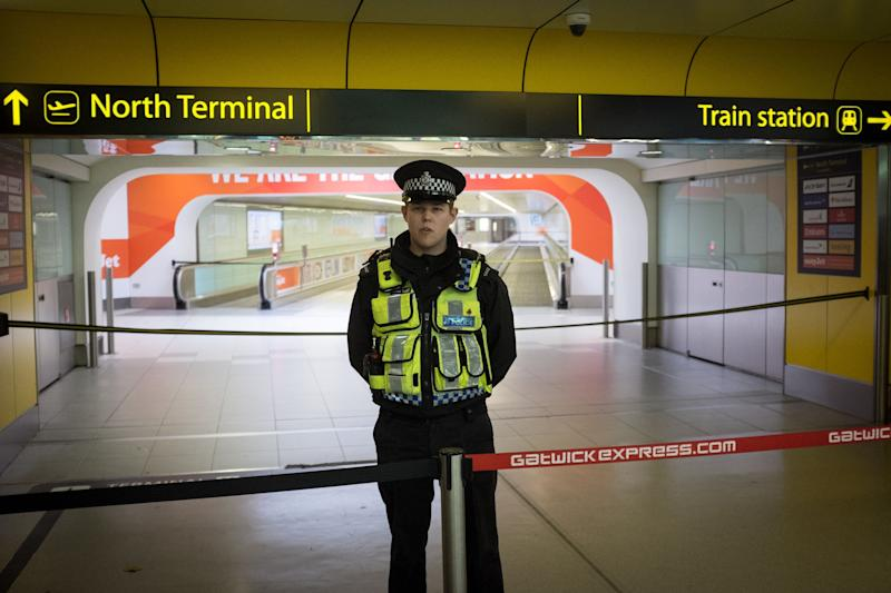 "A police officers stands in front of an area of Gatwick Airport's North Terminal which has been cordoned off, as a 41-year-old man from France is being questioned by police after ""what appears to be a firearm"" was discovered at the airport, Sussex Police said."